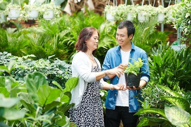 Улыбающийся молодой человек помогает матери выбрать растения и цветы для своего дома