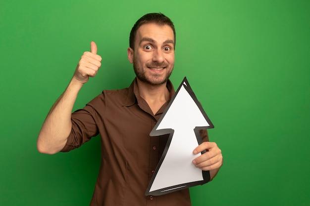 녹색 벽에 고립 된 엄지 손가락을 보여주는 전면을보고 가리키는 화살표 표시를 들고 웃는 젊은 남자