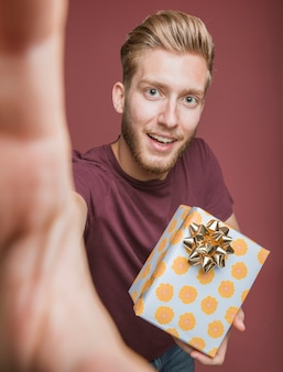 Smiling young man holding floral present with golden bow taking selfie