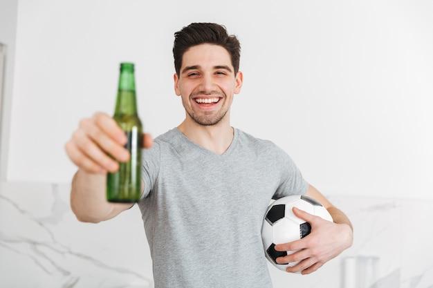 屋内でサッカーとビール瓶を持って笑顔の若い男