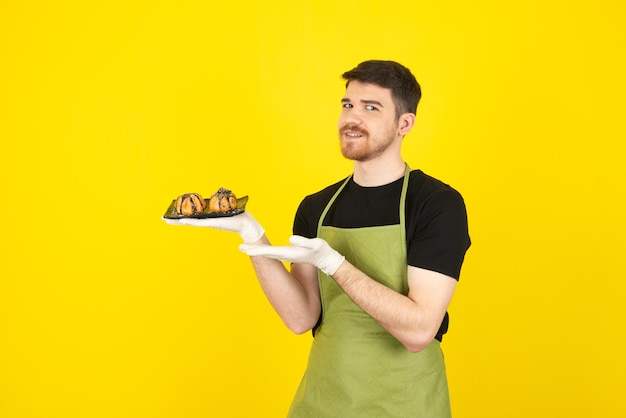 Smiling young man holding fresh homemade muffins and pointing hand at it on a yellow.