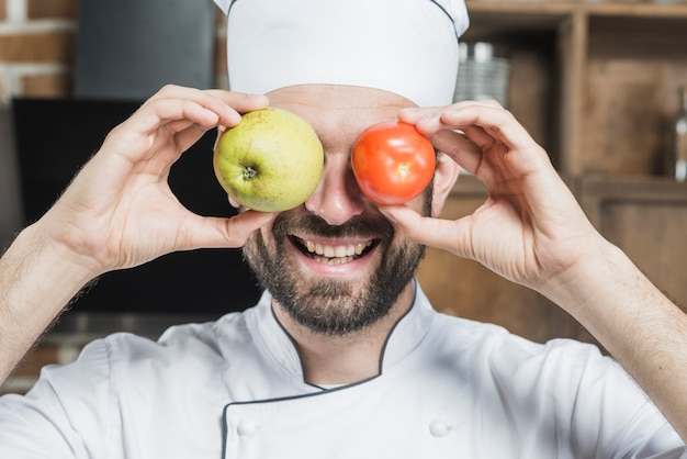 Smiling young man holding fresh ripe tomato and apple in front of his eyes