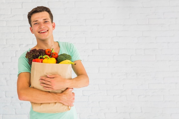 Smiling young man holding fresh vegetables and fruits in grocery paper bag