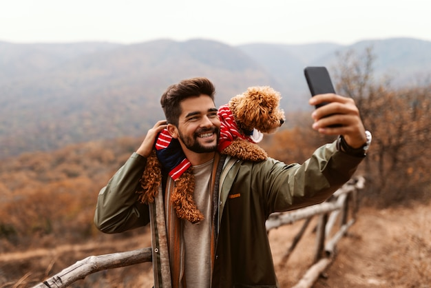 Smiling young man holding his apricot poodle on shoulders and taking self portrait while standing outdoors at autumn