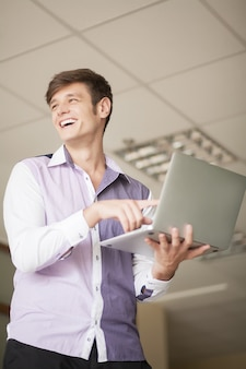 Smiling young man holding laptop and typing