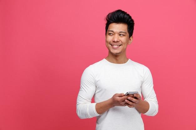 横を見て携帯電話を持って笑顔の若い男