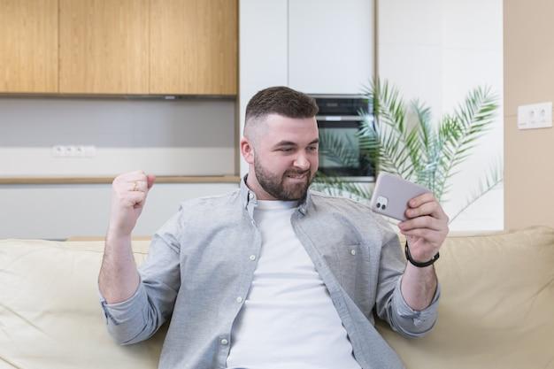 집에서 소파에 앉아 축하하는 동안 휴대 전화를 들고 웃는 젊은 남자