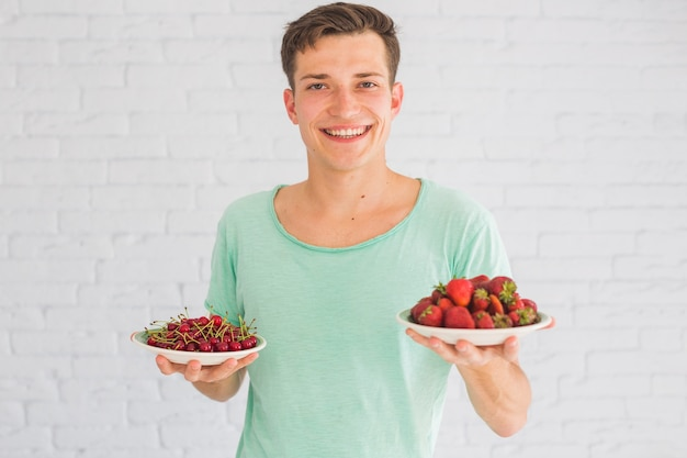 Smiling young man holding plates of strawberries and cherries