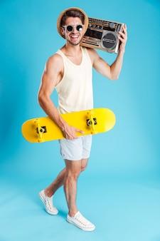 라디오와 노란색 스케이트보드를 들고 웃는 젊은 남자