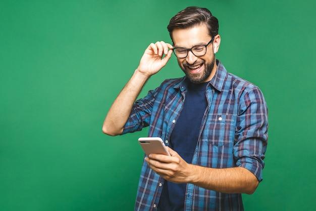 스마트 폰 들고 그것을보고 웃는 젊은 남자. 녹색 배경 위에 고립 된 휴대 전화를 사용 하여 행복 한 남자의 초상화.