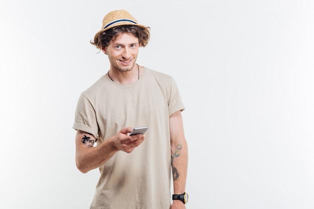 Улыбающийся молодой человек, держащий смартфон, изолированные на белом фоне