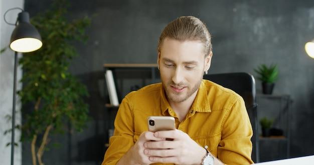 オフィスで手でスマートフォンを保持している若い男の笑みを浮かべてください。