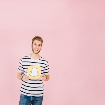 Smiling young man holding snapchat icon on pink background