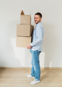 Smiling young man holding stack of cardboard boxes in hands at his new home