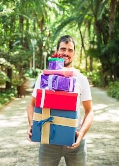 Улыбающийся молодой человек, держащий стопку подарков в парке
