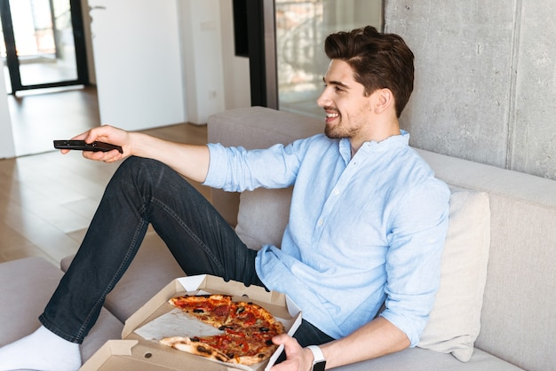 Улыбающийся молодой человек, держащий пульт от телевизора