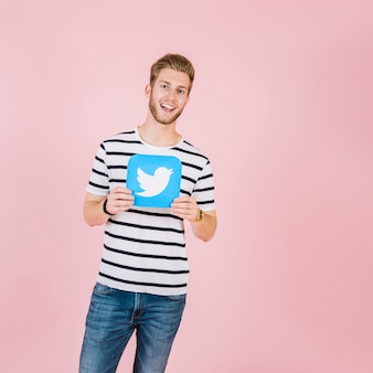 Smiling young man holding twitter icon over pink background