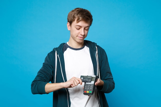Smiling young man holding wireless modern bank payment terminal to process and acquire credit card payments isolated on blue wall. people sincere emotions, lifestyle concept.