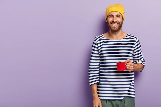 Il giovane sorridente tiene la tazza rossa, beve bevanda calda, indossa un cappello giallo e un maglione a righe casual, ha un'espressione felice, gode del tempo libero, isolato su sfondo viola, spazio vuoto per la tua promozione