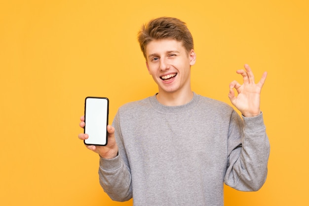 Smiling young man holds a smartphone with a blank screen and shows an ok sign on a yellow