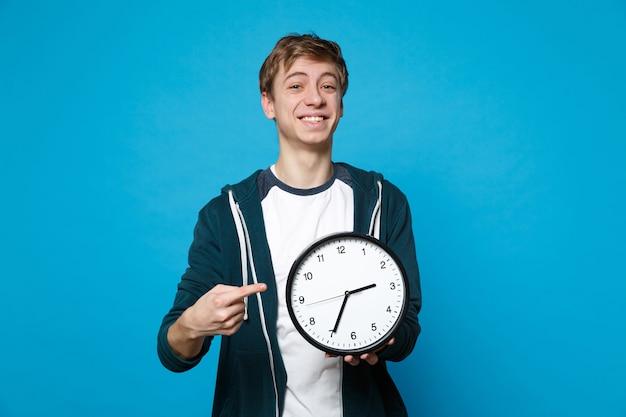 Улыбающийся молодой человек в повседневной одежде держит, указывая указательным пальцем на круглые часы, изолированные на синей стене. время уходит. концепция образа жизни искренние эмоции людей.