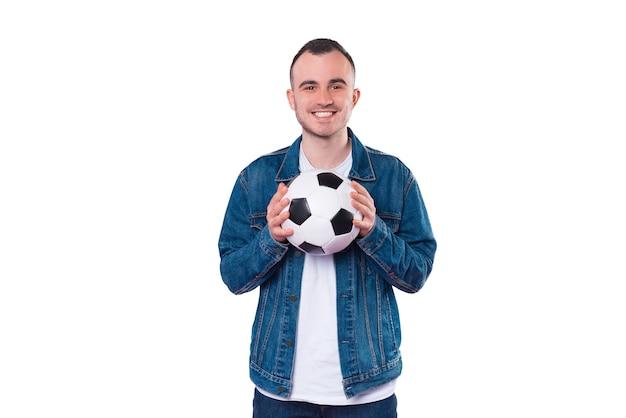 Улыбающийся молодой человек в непринужденной обстановке держит футбольный мяч