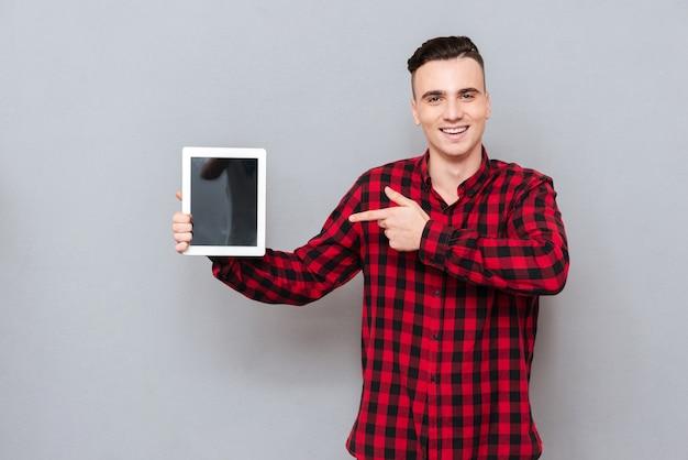 Улыбающийся молодой человек в рубашке, показывая пустой экран планшета и указывая на него. изолированный серый фон