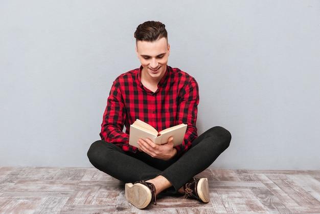 Улыбающийся молодой человек в рубашке сидит на полу и читает книгу. изолированный серый фон Premium Фотографии