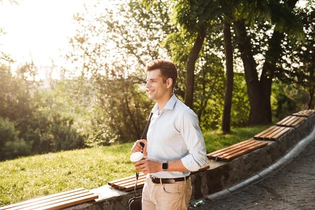 都市公園を歩いてシャツを着た若い男に笑みを浮かべて