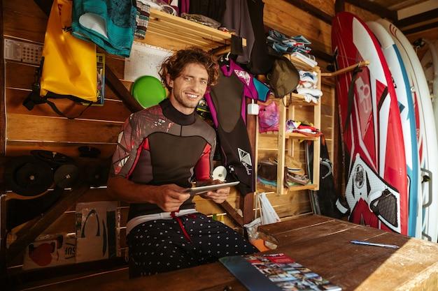 서핑 오두막에 앉아있는 동안 pc 태블릿을 사용하여 수영복에 웃는 젊은 남자