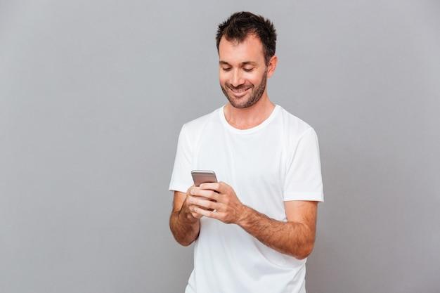 灰色の背景の上のスマートフォンを使用して白いシャツを着て若い男を笑顔