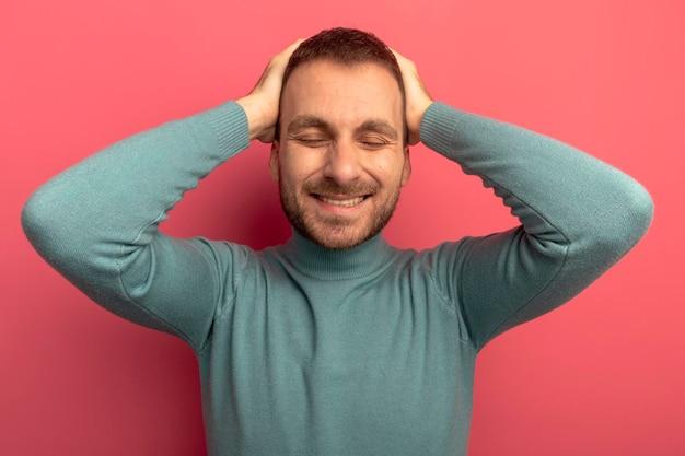 Giovane sorridente che tiene le mani sulla testa con gli occhi chiusi isolati sulla parete rosa