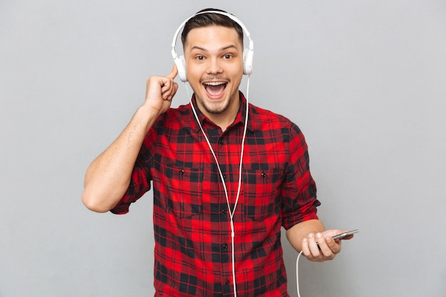 Smiling young man listening music with headphones.