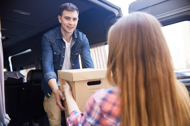 Smiling young man loading moving van