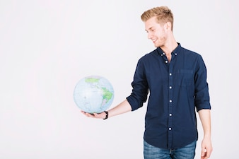 Smiling young man looking at globe