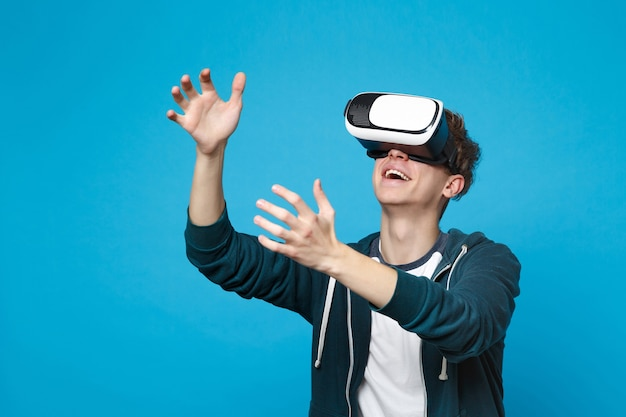 Smiling young man looking on headset touch something like push click on button, pointing at floating virtual screen isolated on blue wall . people emotions lifestyle concept.