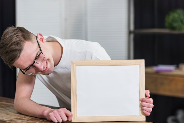 Smiling young man looking at white wooden board on table