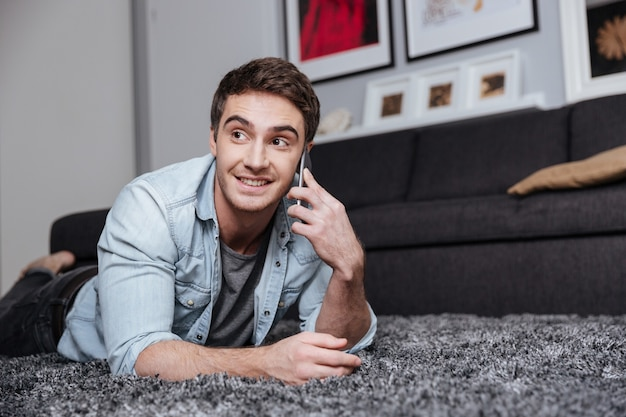 Smiling young man lying on a carpet and using mobile phone at home