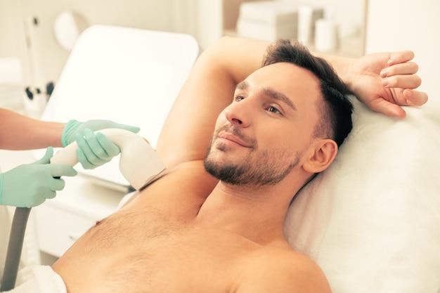 Улыбающийся молодой человек, лежащий на подушке с одной рукой за голову и с лазерной эпиляцией на подмышке