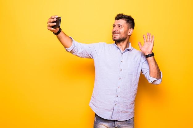 若い男の笑みを浮かべて、黄色の背景の上に孤立した携帯電話立ってselfieを作ります。