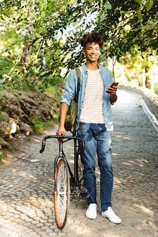 야외에서 젊은 남자를 웃 고, 자전거와 함께 산책