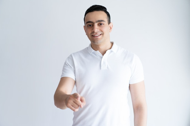 Smiling young man pointing at you and looking at camera. guy choosing viewer.