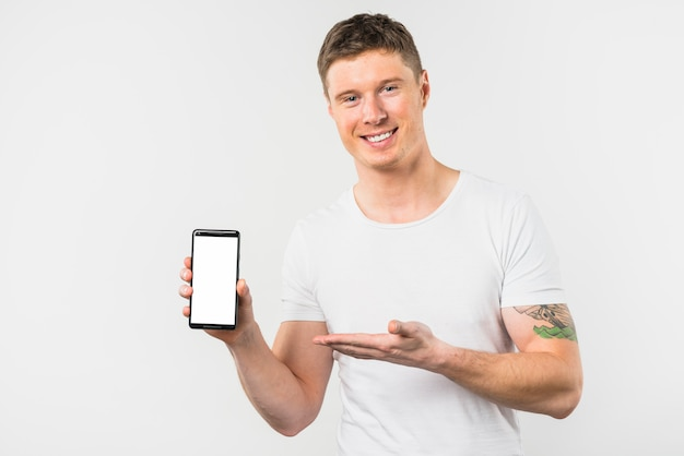 Smiling young man presenting this new smart phone with white display screen