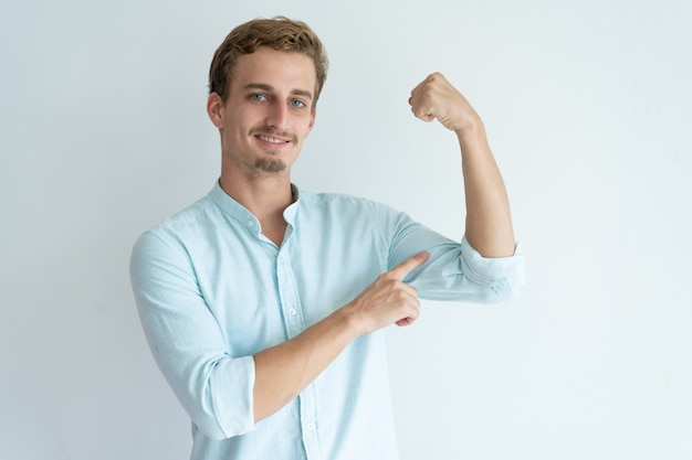 Smiling young man pumping fist and pointing at bicep.