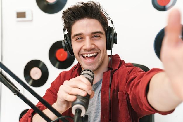 온라인 쇼를 위해 팟캐스트 녹음을 하는 웃고 있는 젊은 남자 라디오 진행자