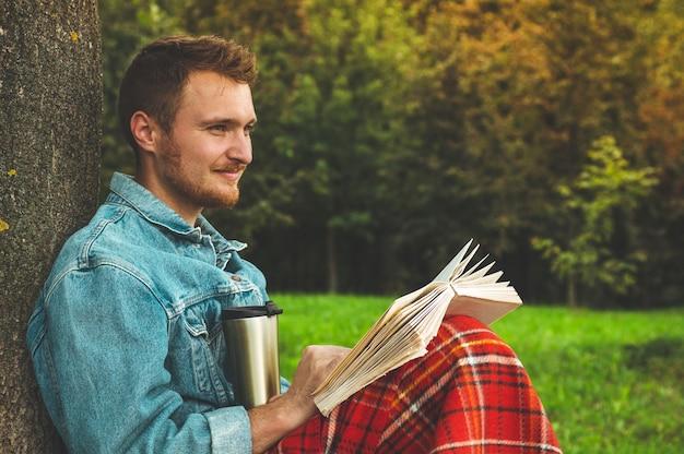 Улыбающийся молодой человек, читающий книгу, открытый с теплым красным пледом и чашкой чая. осенние каникулы и концепция образа жизни.