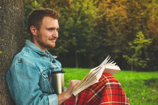 Smiling young man reading book outdoor with a warm red plaid and a cup of tea. autumn vacations and lifestyle concept.