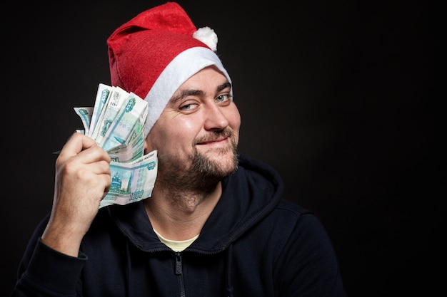 Smiling young man in santa's hat with a bundle of money in his teeth. close-up.