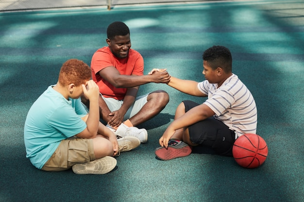 彼らが地面に座ってバスケットボールの試合の後に休んでいる間、10代の少年の手を振って笑顔の若い男