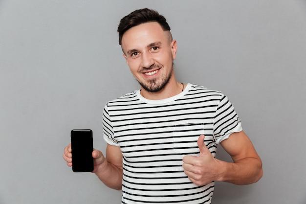 Giovane sorridente che mostra esposizione del telefono cellulare